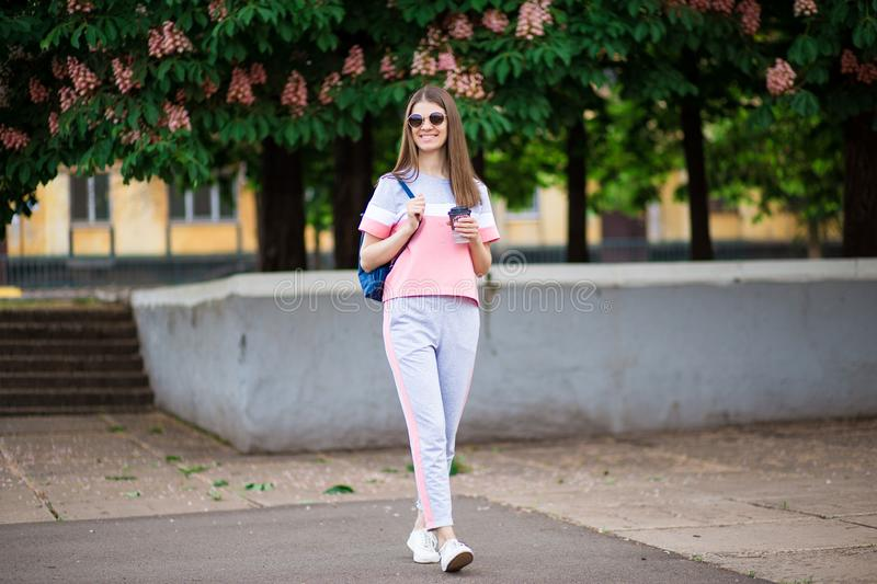 Take away coffee. Beautiful girl in sunglasses with backpack walk by summer street with coffee. stock photography