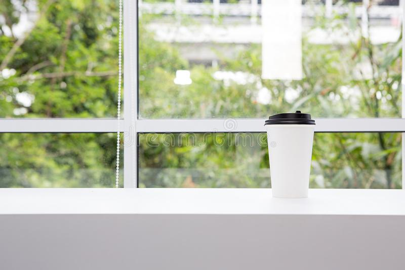 Take away coffee cup placed on white windowsill. Background is a train in the capital. Thailand stock image