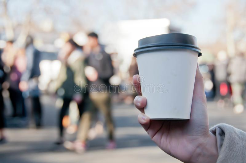 Take away white paper hot coffee cup with right hand holding in Sunday flea market stock photos