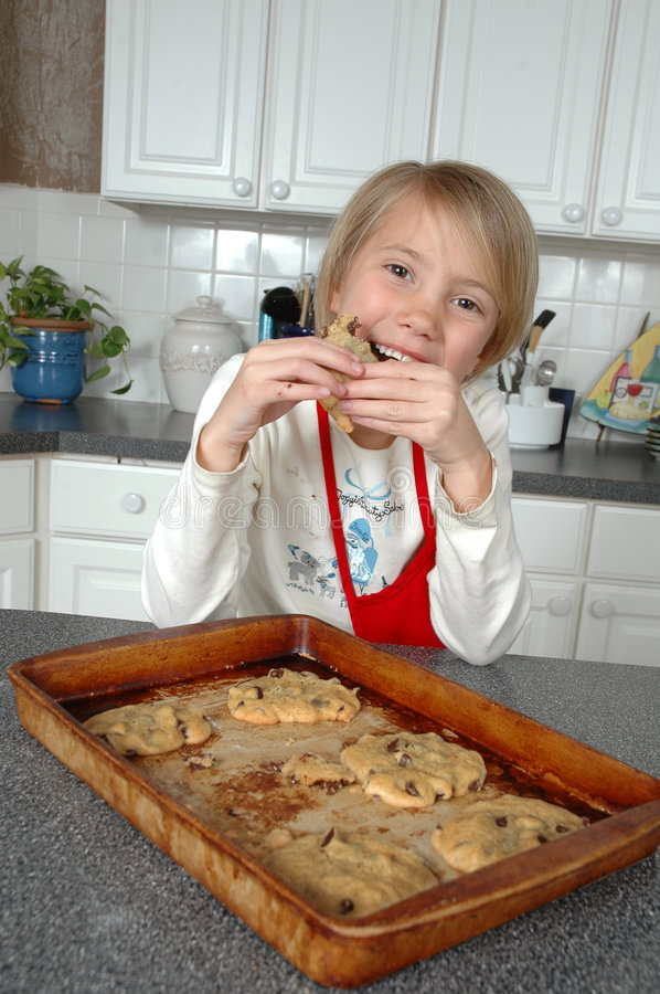 Take a Bite!. Littel girl enjoys eating her chocolate chip cookies as she takes a big messy bite stock photography
