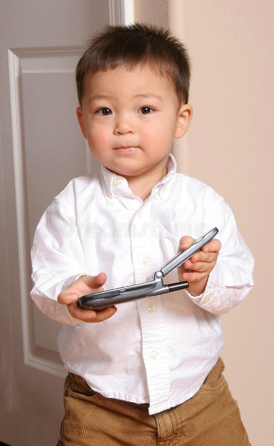 Take the Call. A toddler boy answering the cell phone stock photos