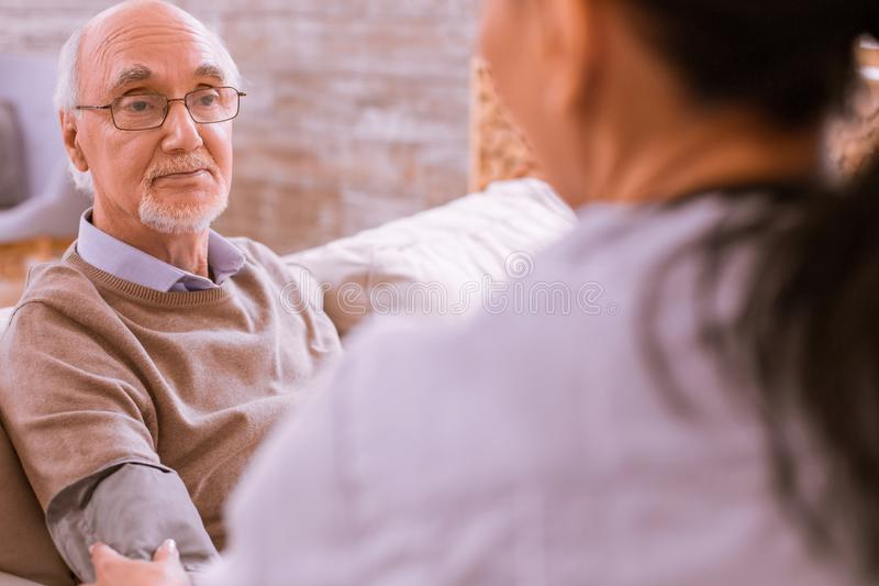 Serious senior man being in all ears stock photography