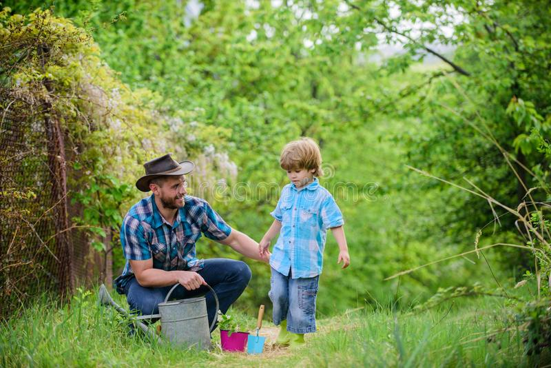 Take care of plants. Boy and father in nature with watering can. Gardening tools. Dad teaching little son care plants. Little helper in garden. Make planet stock photo
