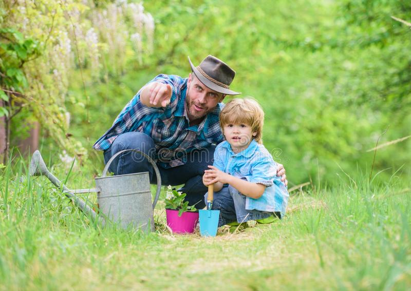 Take care of plants. Boy and father in nature with watering can. Gardening tools. Planting flowers. Dad teaching little. Son care plants. Little helper in stock photo