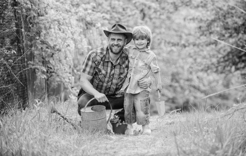 Take care of plants. Boy and father in nature with watering can. Spring garden. Dad teaching little son care plants. Little helper in garden. Planting flowers royalty free stock photography