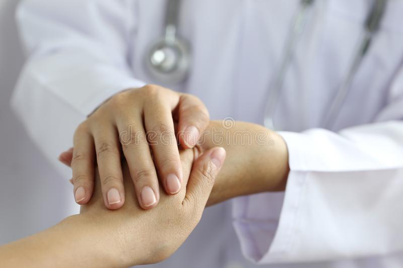 Take care and trust concept, Doctor holding hands of patient at hospital.  stock image