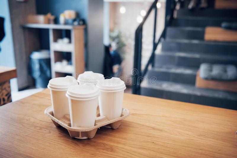 Take coffee to work for the entire office. High angle shot of a cardboard take out tray with four coffee cups with lids stock photos