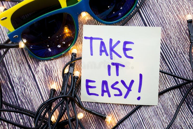 Take it easy A handwritten motivational quote. positive attitude words on the wooden background with two sunglasses of various col stock image