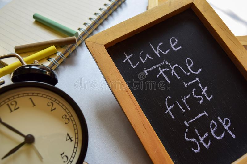 Take the first step phrase colorful handwritten on chalkboard, alarm clock with motivation and education concepts. stock photos