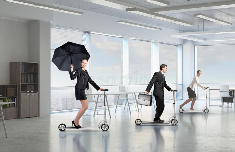 Take a five minute break. Young cheerful businesspeople riding scooter in office stock images
