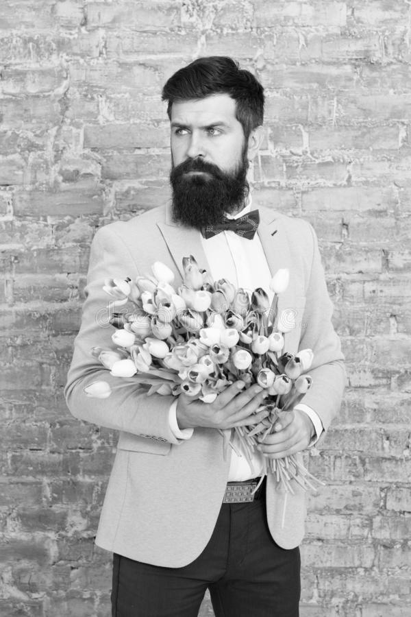 We take flowers personally. Spring gift. Bearded man hipster with flowers. Love. international holiday. Womens day. March 8. Bearded man with tulip spring stock photo