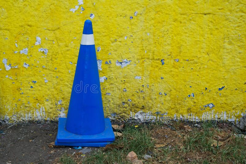 Vehicular control cone in royal blue color against a yellow wall royalty free stock photography
