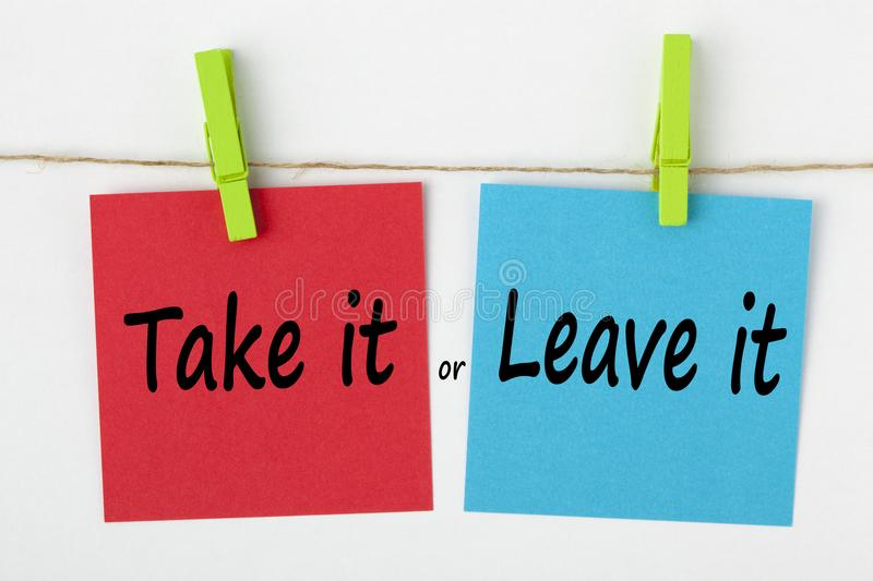 Take it or Leave it concept. Take it or Leave it written on color notes with wooden pinch on white background. Business Concept stock image