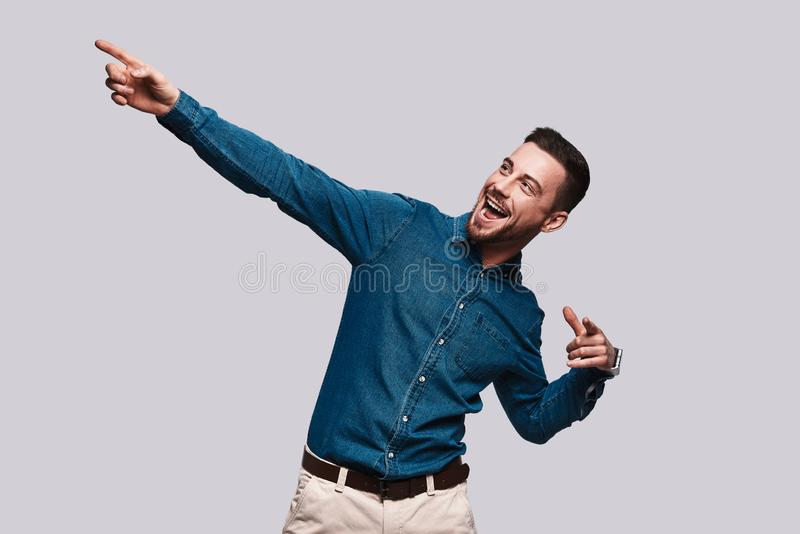 Take a look!. Handsome young man pointing copy space and smiling while standing against grey background royalty free stock photos