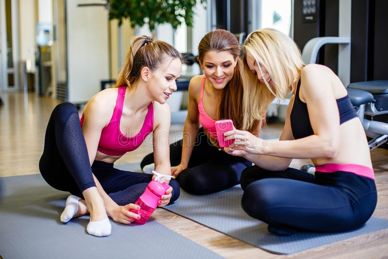 Take a look at my workout plan! Beautiful young women in sportswear discussing something with smile and using smartphone while sit stock image