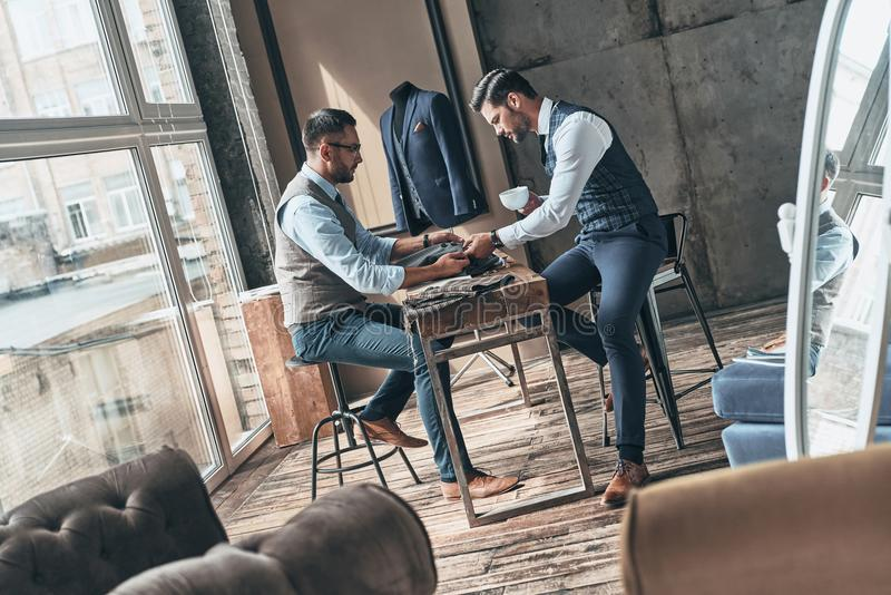Take a look at this one. Young fashionable designer choosing fabric with his client while sitting in the workshop royalty free stock photo