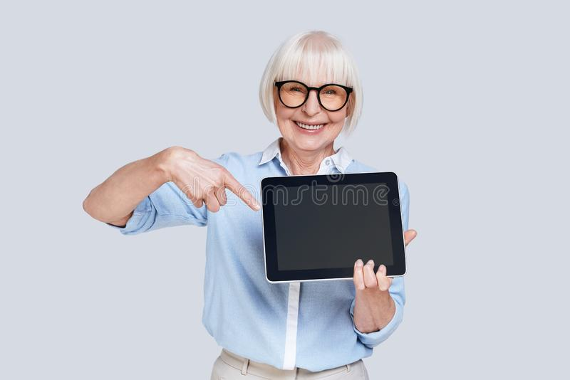 Take a look over here!. Beautiful senior woman pointing at digital tablet and smiling while standing against grey background stock photography