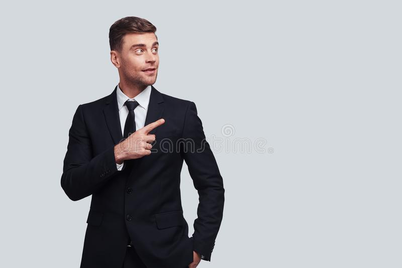 Take a look over there!. Good looking young man in full suit pointing copy space and smiling while standing against grey background stock photos