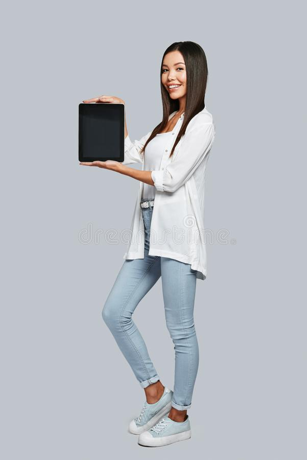 Take a look!. Full length of attractive young Asian woman pointing copy space on her digital tablet and smiling while standing against grey background stock photo