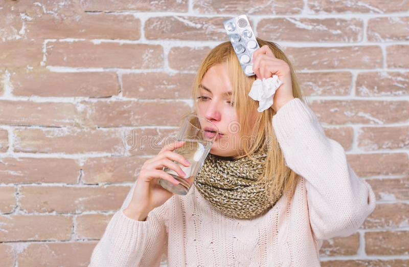Take medications to reduce fever. What to know about breaking fever. Woman tousled hair scarf hold glass water and. Tablets blister. Girl suffer fever and take royalty free stock images
