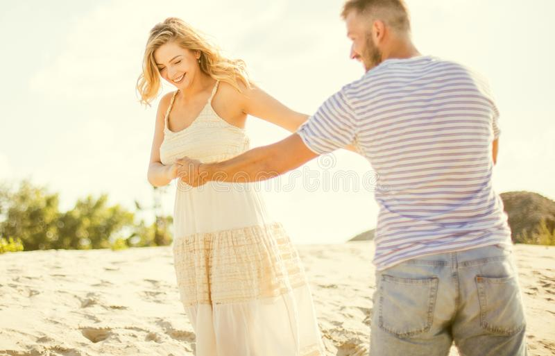 Take my hands and dance with me. Young couple having fun on sand royalty free stock photo