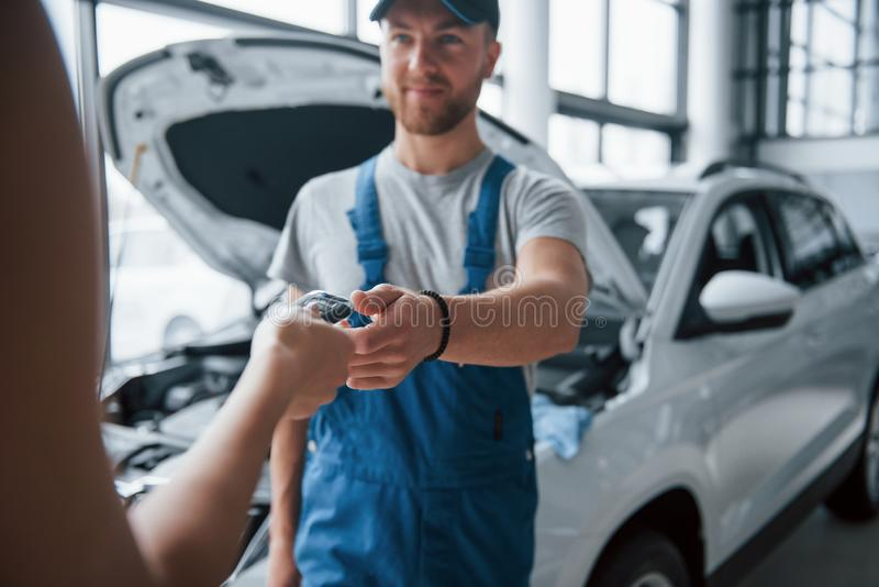 Take my keys. Woman in the auto salon with employee in blue uniform taking her repaired car back royalty free stock photo