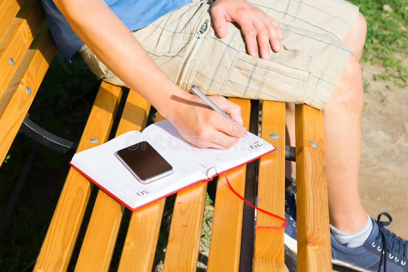 Take notes on a bench in a diary royalty free stock photo
