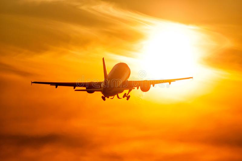Take-off of a passenger airplane directly to the rising morning sun. Take-off of a passenger aircraft directly to the rising morning sun royalty free stock photo
