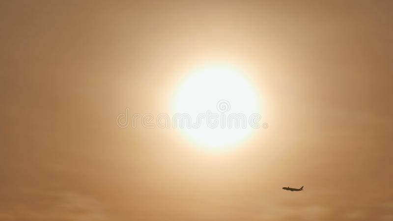 Take off the plane in the distance against the background of sunrise or sunset. Silhouette of an airplane. Airplane in stock image