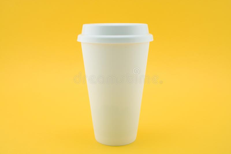 Take-out coffee cup from coffee shop on yellow background. Coffee paper cup royalty free stock photo