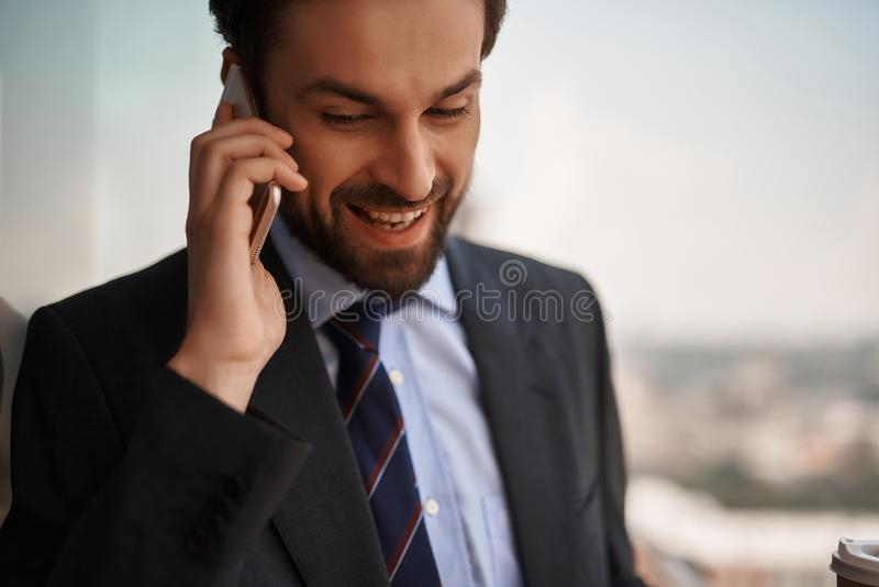 Man in office suit talking by phone on balcony. Take a pause. Close up portrait of cheerful businessman talking by phone while standing on balcony stock photography