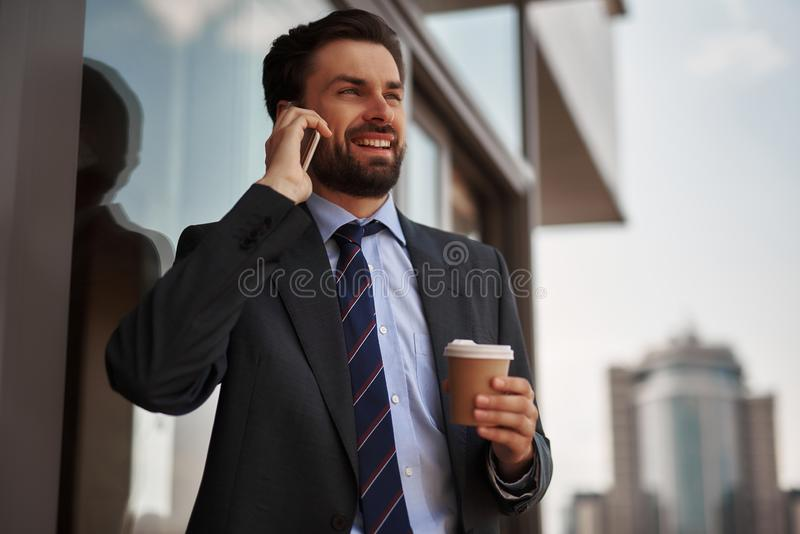Man in office suit talking by phone on balcony. Take a pause. Close up portrait of cheerful businessman talking by phone while standing on office balcony with royalty free stock images