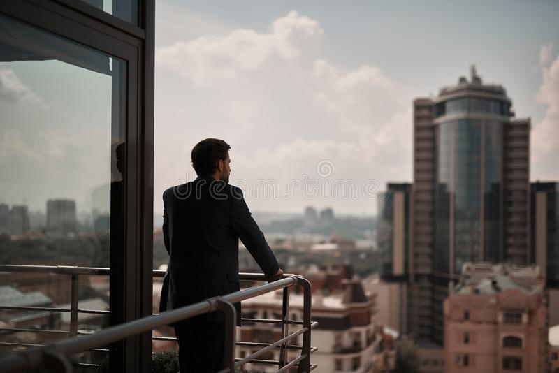Male in office suit being on balcony. Take a pause. Full length back side portrait of businessman thoughtful standing on office balcony. Copy space on right royalty free stock photo