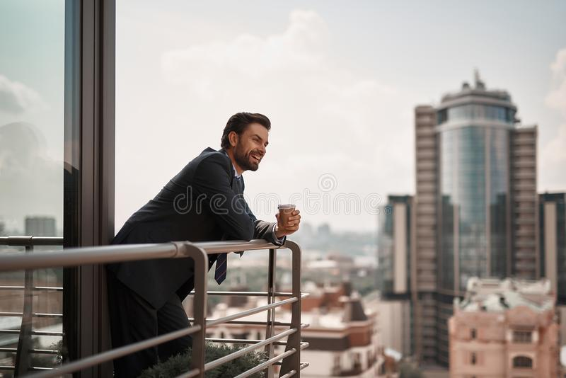 Man in office suit standing on balcony. Take a pause. Full length portrait of cheerful businessman enjoying city view on office balcony with cup of coffee. Copy stock images