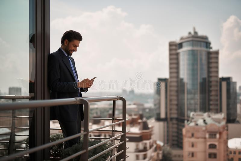 Man in office suit reading massages on phone royalty free stock images