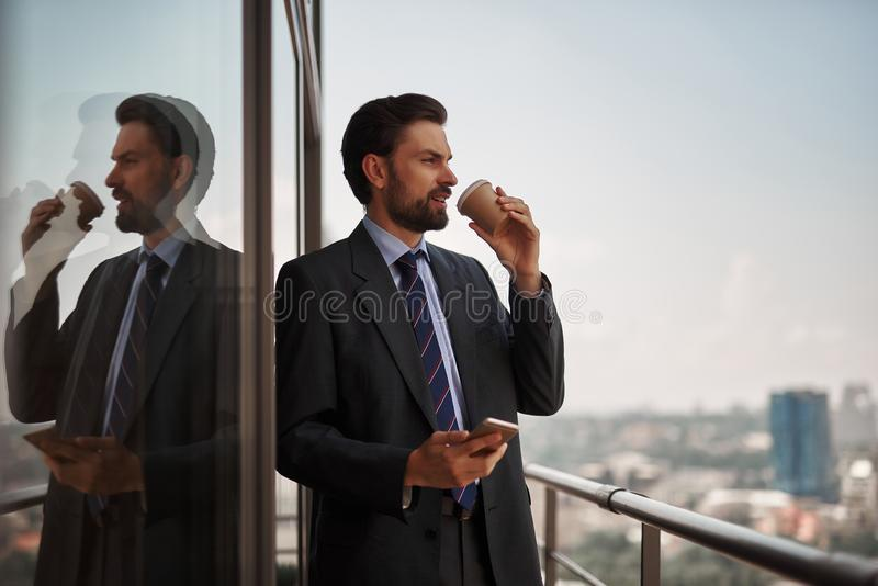 Man in office suit drinking coffe on balcony. Take a pause. Waist up portrait of smiling businessman drinking coffee on office balcony after talking by phone royalty free stock photo