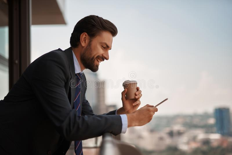 Man in office suit reading massages on phone royalty free stock photo