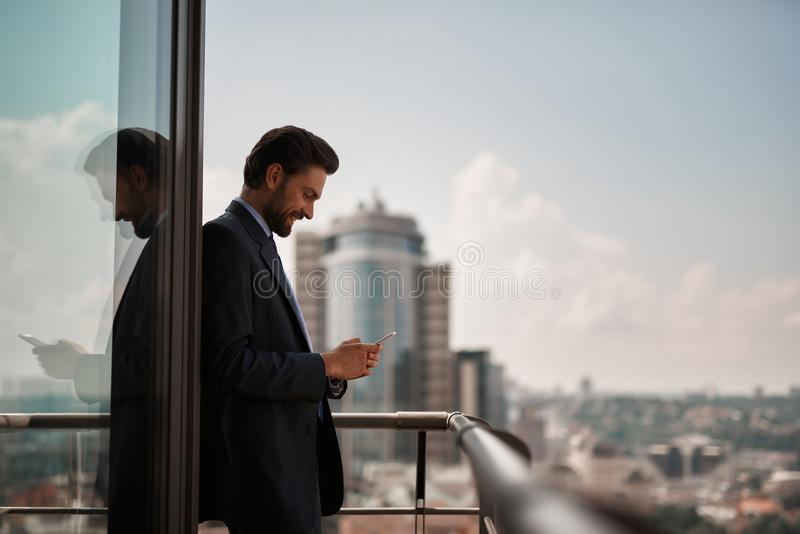 Man in office suit checking massages on phone. Take a pause. Waist up portrait of smiling businessman reading massages on smartphone while standing on office royalty free stock photo