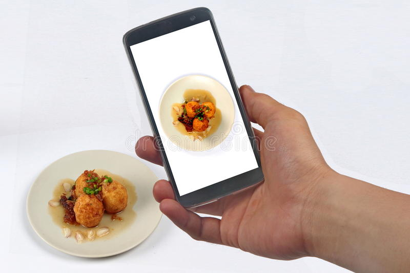 Take photo fried hard-boiled eggs with tamarind sauce for share. Use mobile phone to take photo a dish of fried hard-boiled eggs with tamarind sauce call as royalty free stock image