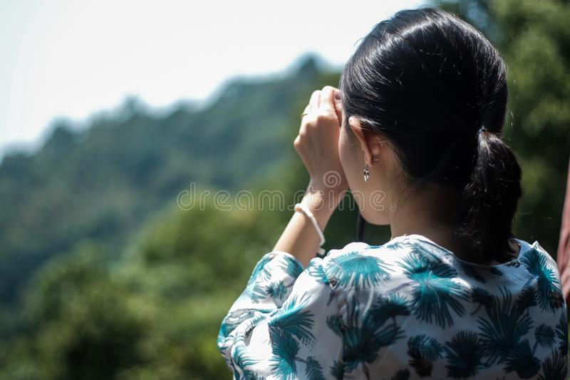 Take a picture. Asian tourist girl take a picture in the wild photography lifestyle backpacker woman summer taking lady camera travel nature people smile outdoor stock image