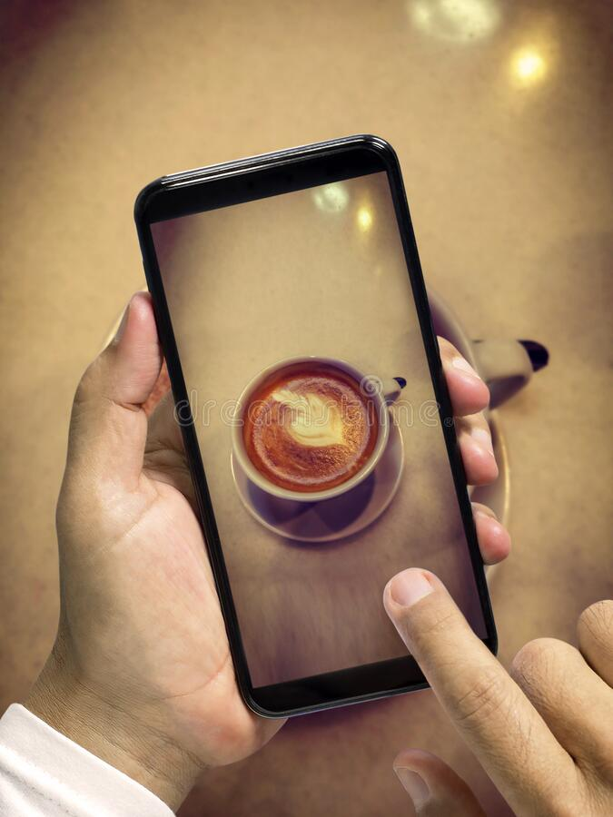 Take pictures of the coffee cup with smartphone mobile. Man`s hand holding a smart phone photography beautiful cup of coffee stock image