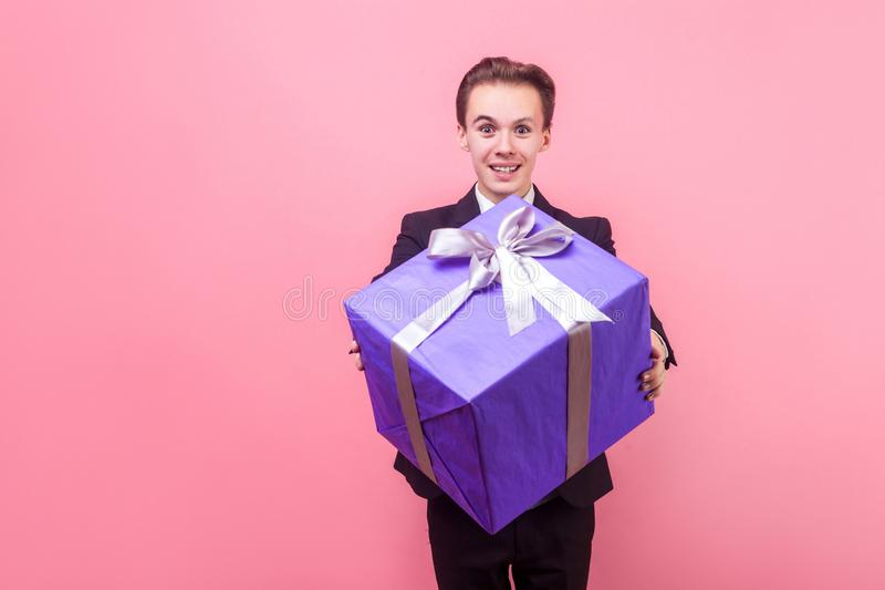 Take it! Portrait of positive generous man in suit holding out gift box and smiling. studio shot isolated on pink background. Take it! Portrait of positive royalty free stock photography