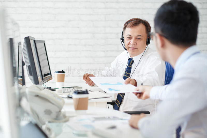 Take this report. Stock broker giving last financial report to coworker stock photo