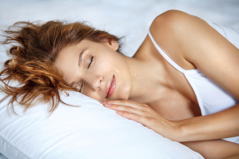 Take a rest. Beautiful brunette woman lying on a pillow stock images