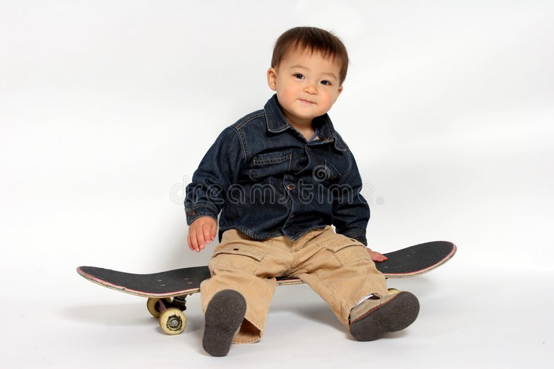 Take a ride. A toddler boy posing on a skateboard stock images