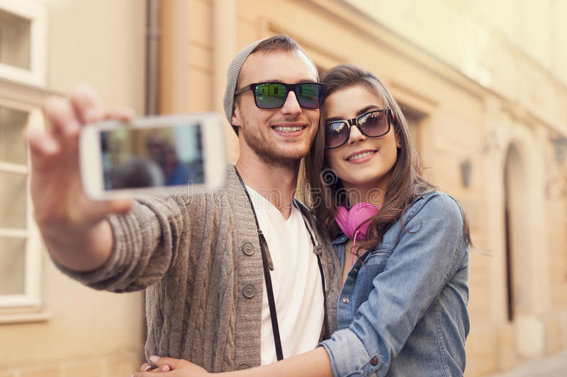 Take a selfie. Fashionable couple taking selfie by mobile phone royalty free stock photos