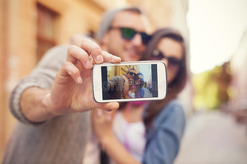 Take a selfie. Young couple taking selfie in the city royalty free stock images