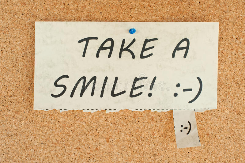 Take a smile. Tear off paper notice on a corkboard royalty free stock image
