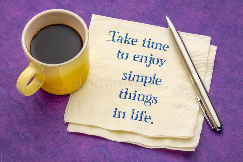 Take time to enjoy simple things in life. Handwriting on a napkin with a cup of coffee against colorful textured paper royalty free stock image