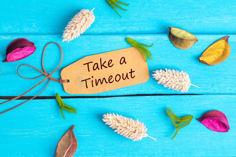 Take a timeout text on paper tag. With rope and color dried flowers around on blue wooden background royalty free stock image